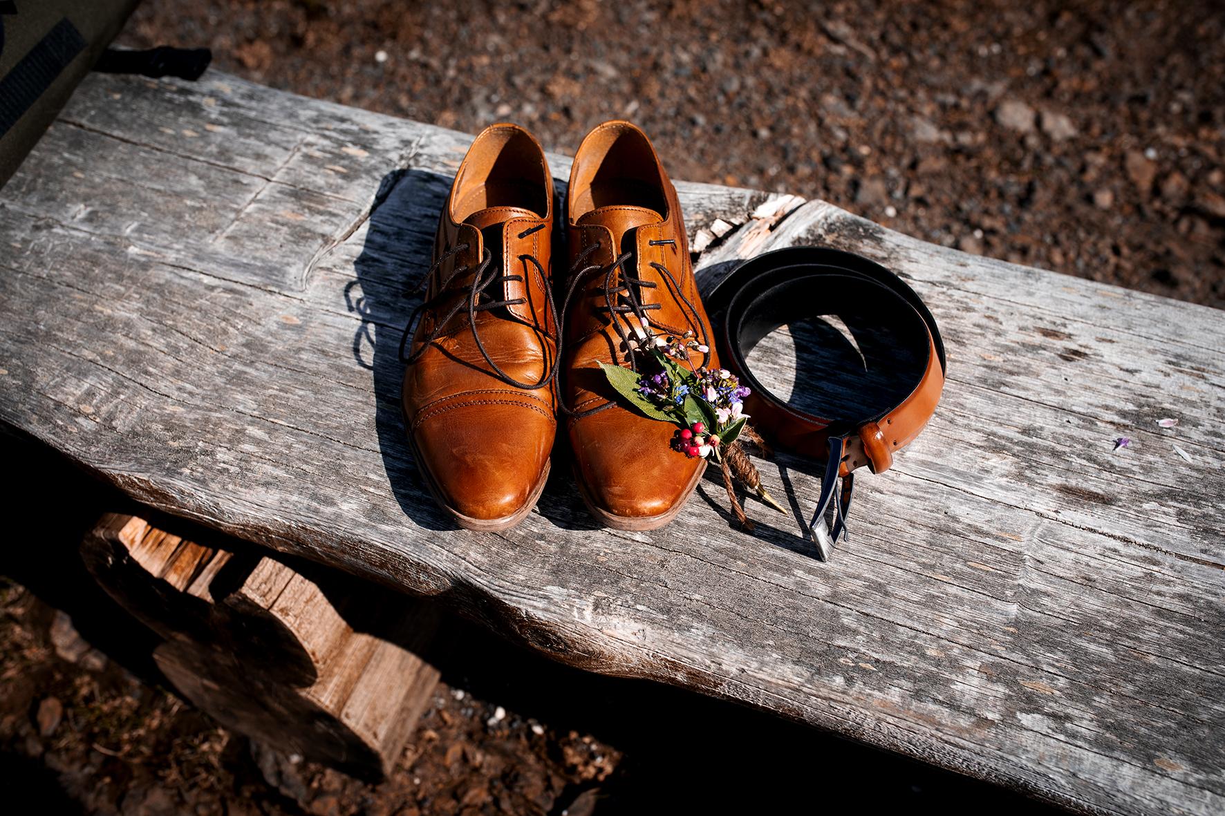 Hellbraune Anzugsschuhe aus Leder, ein dazu passender Gürtel und der Anstecker des Bräutigams liegen bereit auf einer Holzbank. Der Anstecker ist aus saisonalen und regionalen Blüten, Beeren und Salbeiblättern gebunden.