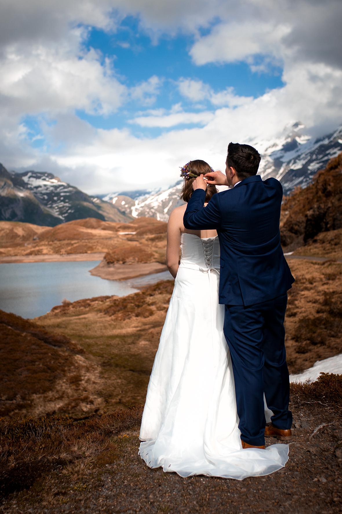 Getting Ready bei einem Elopement in den Alpen. Der Bräutigam bindet der Braut den Blumenkranz um. Das Brautpaar blickt dabei über einen Bergsee und deiner Bergkette mit weissen Gipfeln in der Ferne.
