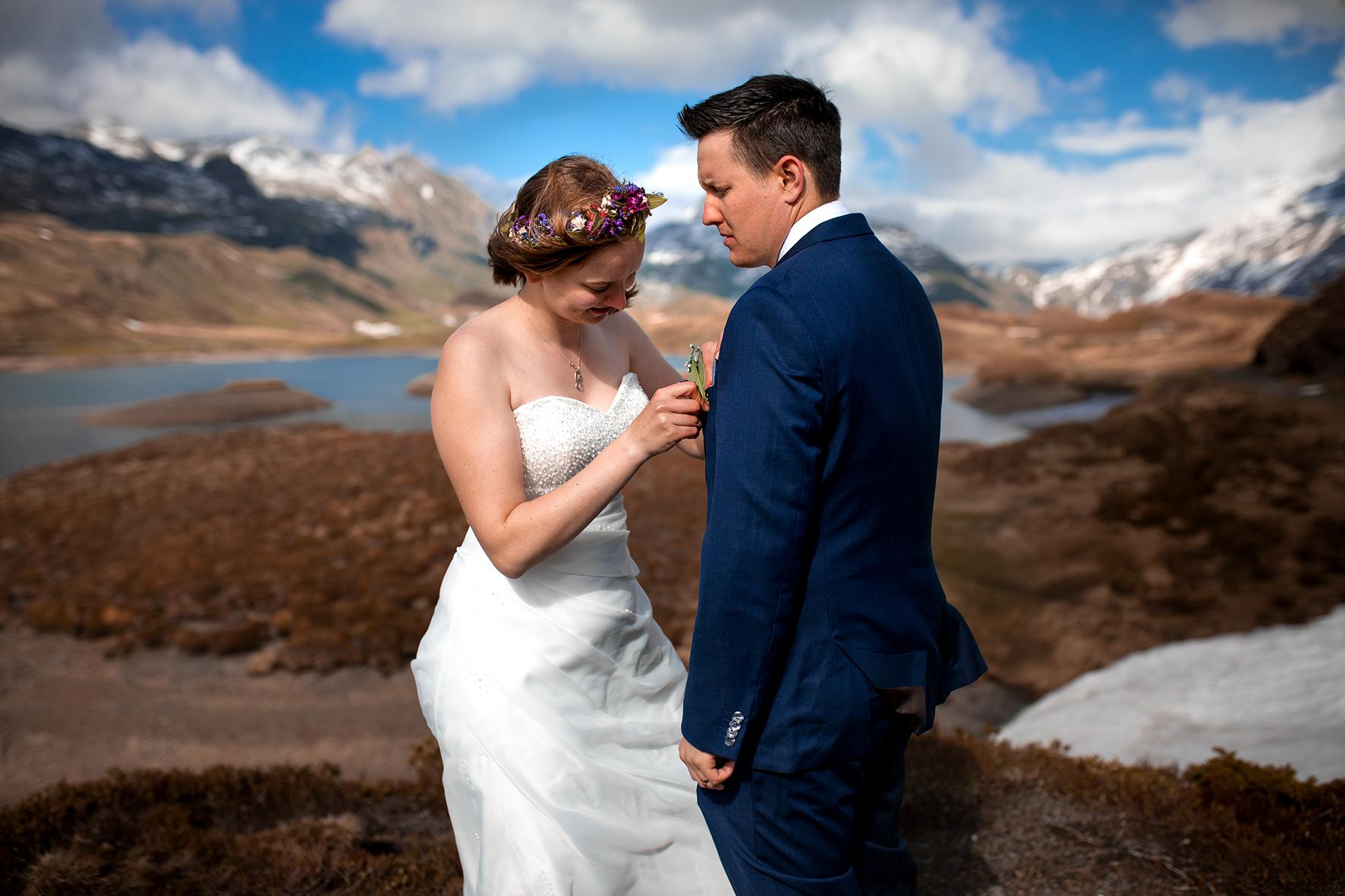 Das Getting Ready bei einer Elopement Hochzeit findet draussen in der Natur statt. Die Braut steckt dem Bräutigam seinen Blumenanstecker an. Der Wind zerzaust dabei der Braut die Frisur. Sie trägt bereits ihr Hochzeitskleid und ein Blumenkranz schmückt ihr Haar. Die Beiden stehen inmitten einer Moorlandschaft der Melchsee Frutt. Im Hintergrung ist der Tannensee zu sehen. Die Berge sind schneebedeckt und die Wolken durchziehen den sonst blauen Himmel. Der letzte Schliff beim Getting Ready in den Schweizer Bergen. Die Braut rückt dem Bräutigam den Anstecker aus regionalen uns saisonalen Blüten und Beeren zurecht.