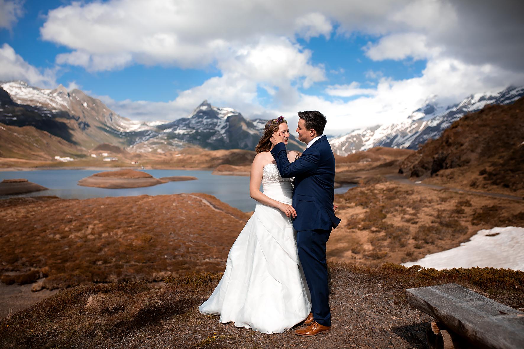 Zärtlich streicht der Bräutigam der Braut eine Haarsträhne aus dem Gesicht. Das Brautpaar sieht sich nach dem Getting Ready zum ersten Mal in ihrem Hochzeitoutfit. Die Braut trägt ein schulterfreies weisses Kleid. Der Bräutigam trägt einen dunkelblauen Anzug und hellbraune Lederschuhe. Das Brautpaar heiratet nur zu Zweit in den Schweizer Bergen. Die Location ist die Hochebene Melchsee Frutt im Kanton Obwalden. Die Beiden stehen vor einem Bergsee, umgeben von weissen Berggipfeln und einer rot braunen Moorlandschaft. Im Hintergrund sind die Häuser und Hütten der Tannenalp zu sehen.