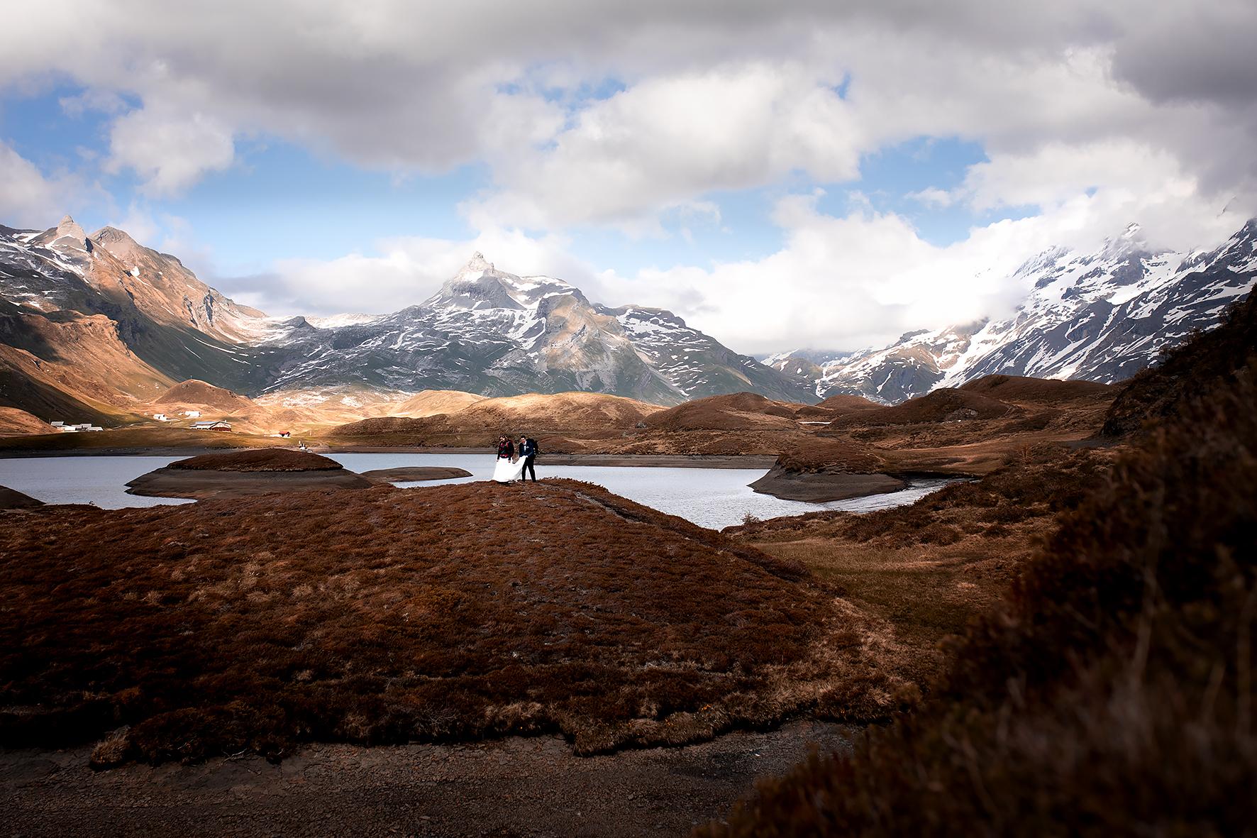 Eine Abenteuerhochzeit in den Schweizer Bergen. Das Brautpaar wandert im Hochzeitskleid und Anzug und mit Rucksack beladen über eine Halbinsel am Tannensee auf der Melchsee Frutt. Der Bräutigam trägt der Braut die Schleppe ihres Hochzeitkleides.