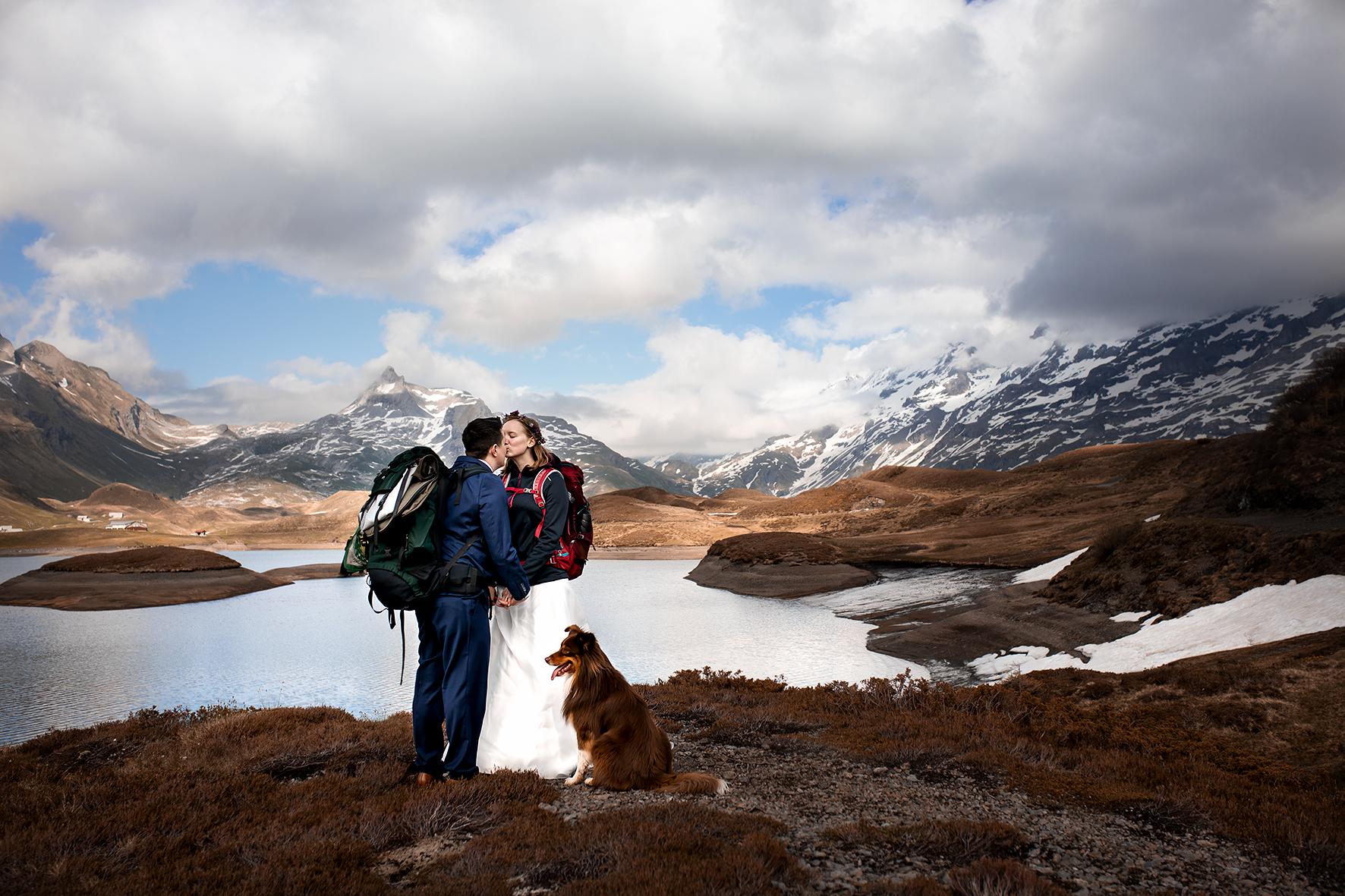 Ein Elopement in der wilden Berglandschaft der Melchsee Frutt im Kanton Obwalden. Das Brautpaar steht inmitten schneebedeckter Gipfel. Im Hintergrund liegt der Tannensee, die Tannenalp und die Lücke Richtung Engelberg. Am Ufer des Bergsees sind noch einige Schneefelder vom Winter. Die Braut trägt ein weisses Hochzeitskleid, Wanderschuhe, eine Jacke wegen dem kühlen Wind und ihren Rucksack. Der Bräutigam trägt Anzug, Anzugsschuhe und einen Wanderrucksack. Die Beiden halten sich an den Händen und küssen sich.