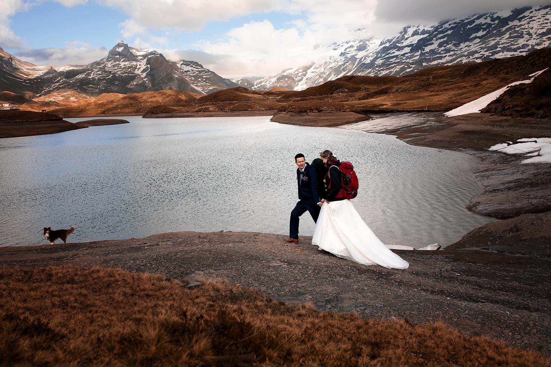 Braut und Bräutigam wandern entlang des Bergsees um einen guten Ort für ihr Trauversprechen zu finden. Das Ufer des Sees ist steinig und teilweise mit Schnee bedeckt und ist von mit Heidekraut bewachsenen Hügeln umgeben. Am Horizont erstreckt sich eine Bergkette mit dem Titlis, dem Graustock, der Wendestöcke und dem Jochstock. Der Hund des Brautpaares ist den Beiden voraus und blickt zurück. Das Paar trägt ihr Hochzeitsoutfit und Rucksäcke.