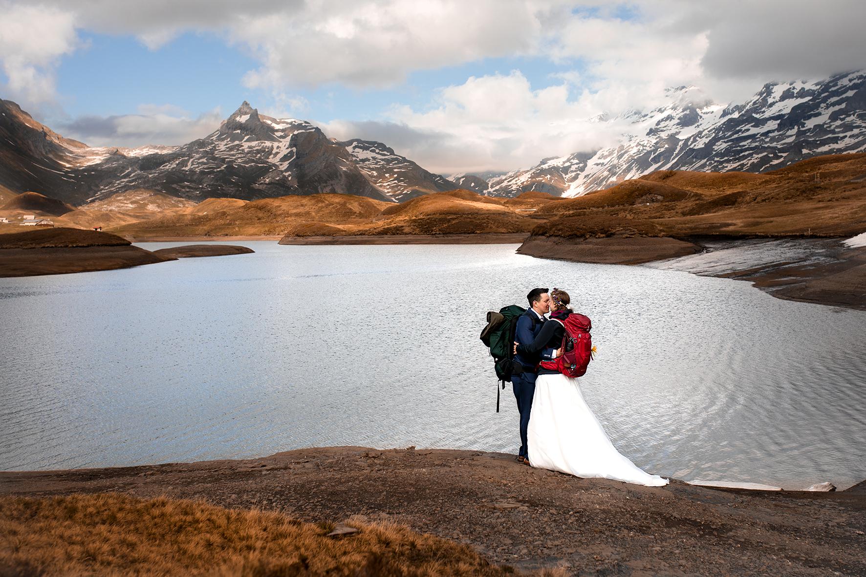 Ein Brautpaar hält sich in den Armen und küsst sich vor einer atemberaubenden Bergkulisse in den Alpen. Ein grosser Bergsee, rostrote Hügel und schneebedeckte Berge bilden die Kulisse für ein Hochzeit in den Bergen. Das Brautpaar trägt Hochzeitsoutfit und Wanderrucksäcke.
