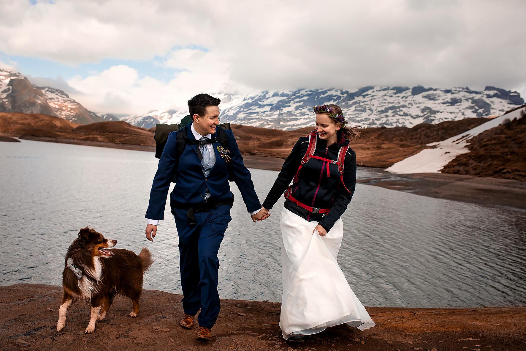Hand in Hand wandert ein Brautpaar am Ufer eines Bergsees. Neben ihnen läuft ein Australian Shepherd Hund. Die Braut hat ihr Kleid mit einer Hand gerafft, um das weisse Hochzeitskleid vom staubigen Felsboden fernzuhalten.