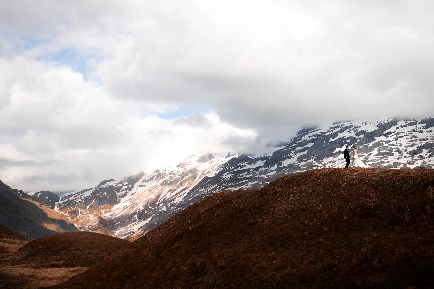 Ganz klein steht das Brautpaar auf einem Hügel vor einer imposanten Bergkulisse. Braut und Bräutigam stehen sich gegenüber und bereiten sich auf ihre Trauzeremonie vor. Die Berge sind teilweise von Schnee bedeckt. Die Sonne bricht an einigen Stellen durch die Wolken und wirft Lichtflecken auf das Tal. Im Hintergrund ist der Jochpass zu sehen.