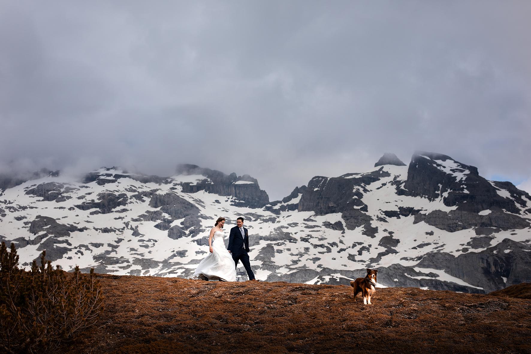 Braut und Bräutigam wandern zusammen über einen Hügel vor einer schneebedeckten Felswand. Ihr Hund geht voraus und hält Wache. Die Stimmung ist mit dem Wolkenspiel eher düster und mystisch.