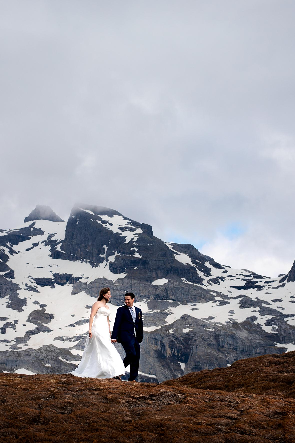 Ein Brautpaar wandert Hand in Hand über einen Hügel auf der Melchsee Frutt. Im Hintergrund eine Felswand mit Schnee. Der Wind bläst der Braut die Haare ins Gesicht.