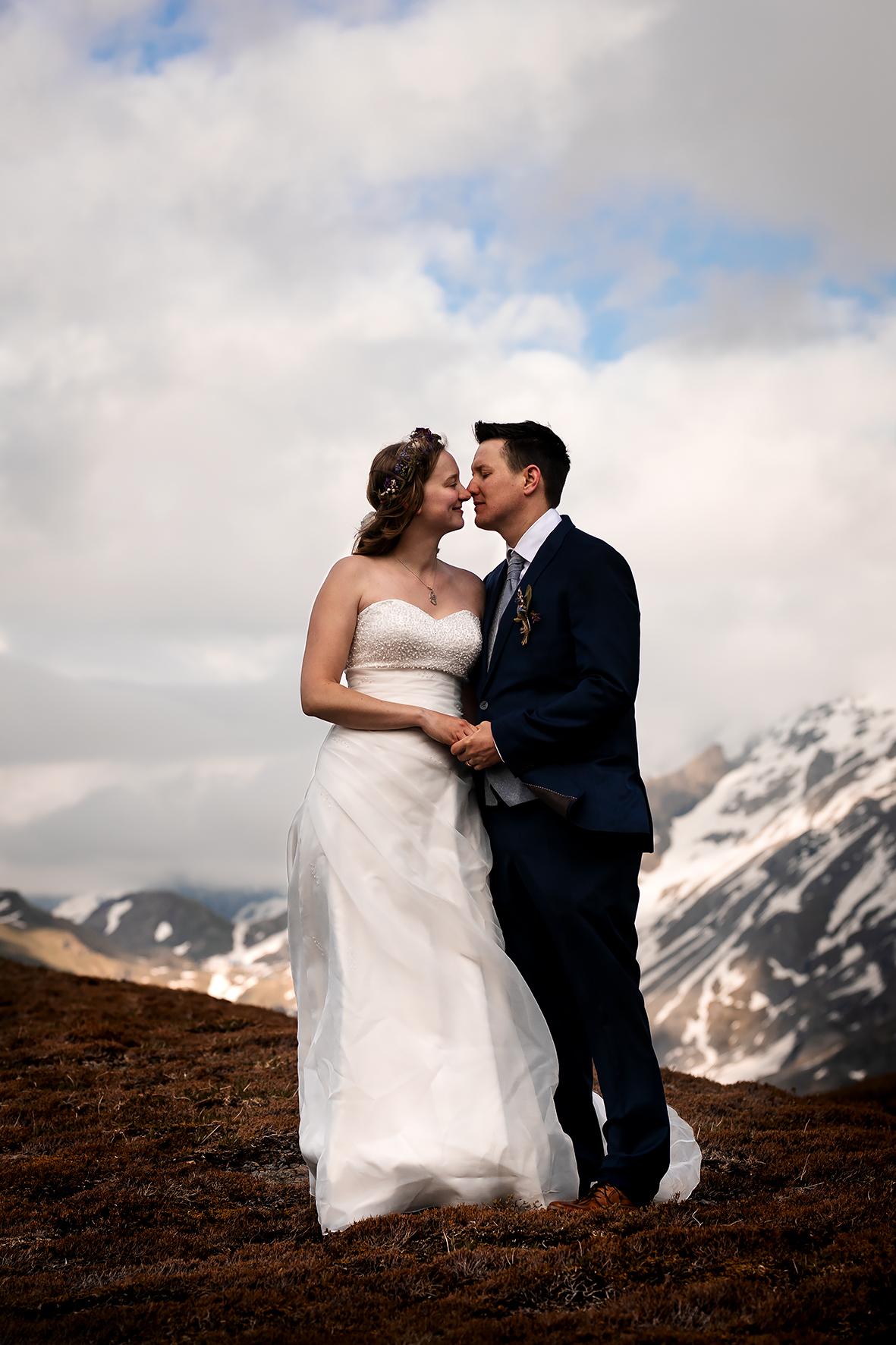 Ein klassisches Portrait von einem Brautpaar in den Bergen. Die Brautleute halten sich an den Händen und legen zärtlich ihre Gesichter aneinander. Die Sonne scheint hinter den Beiden auf den Jochpass über Engelberg. Das Brautpaarshooting ist Teil eines Elopements in den Schweizer Bergen.