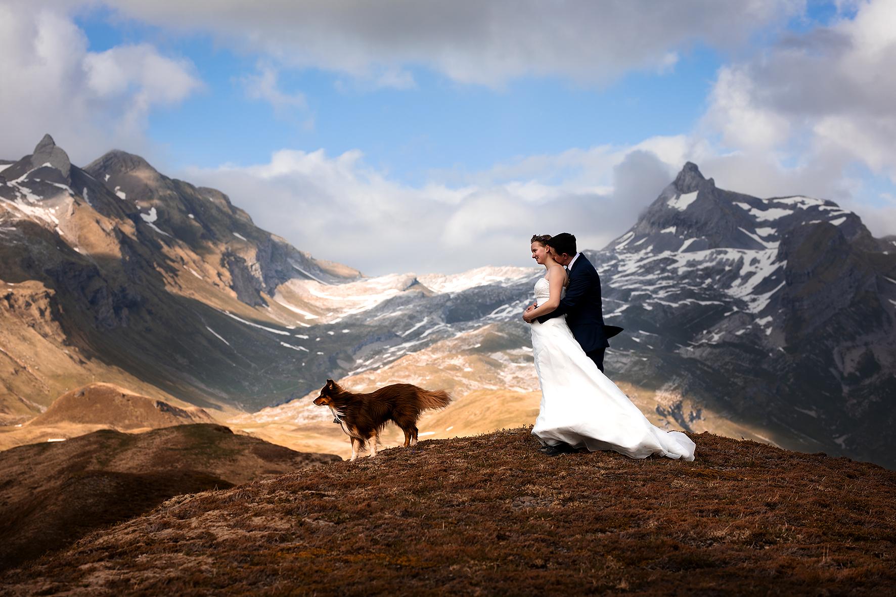 Ein Brautpaarshooting nach dem Trauversprechen anlässlich eines Elopements in den Schweizer Alpen. Der Bräutigam hält die Braut von hinten in einer Umarmung umschlungen und küsst ihren Nacken. Die beiden stehen auf einem Hügel und die Braut blickt in die Ferne. Im Hintergrund sind der Graustock und der Rotsandnollen. Die Sonne bricht durch die Wolken und wirft Flecken auf die Berglandschaft.