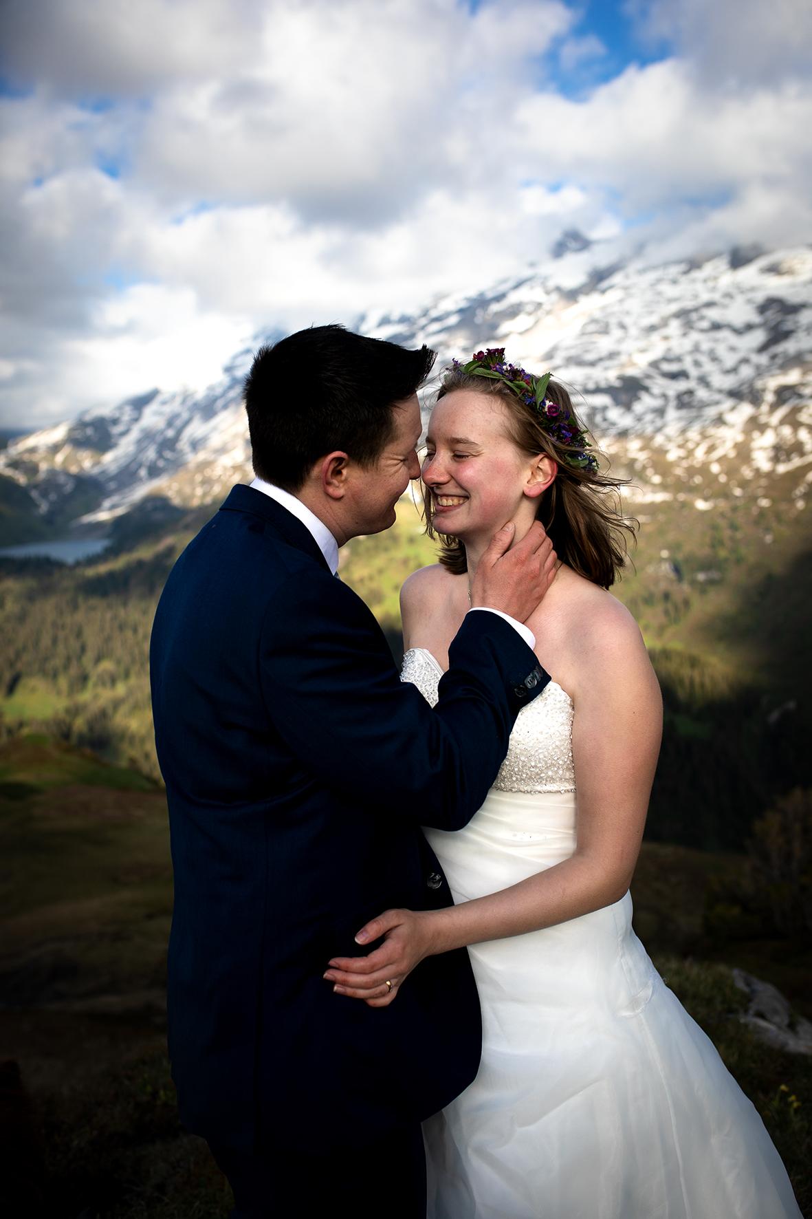 Ein Brautpaar in den Schweizer Alpen gibt sich das Trauversprechen bei einer Hochzeit zu Zweit. Im Hintergrund sind der Engstlensee und der Jochpass zu sehen.