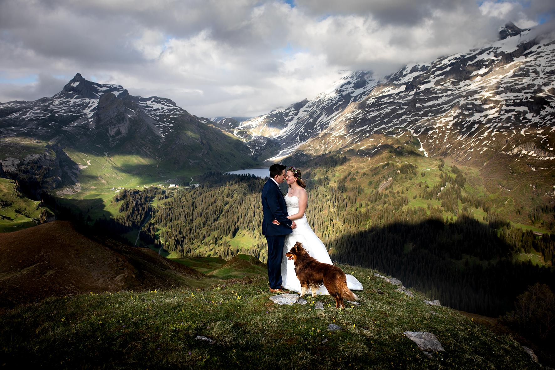 Eine Trauzeremonie während einem Elopement in den Schweizer Bergen. Im Hintergrund die Engstlenalp, der Engstlensee und der Jochpass. Braut und Bräutigam geben sich das Jawort bei einer intimen Hochzeitsfeier nur zu Zweit auf der Melchsee Frutt. Bei der Hochzeit dabei ist ihr Hund, ein Australian Shepherd.