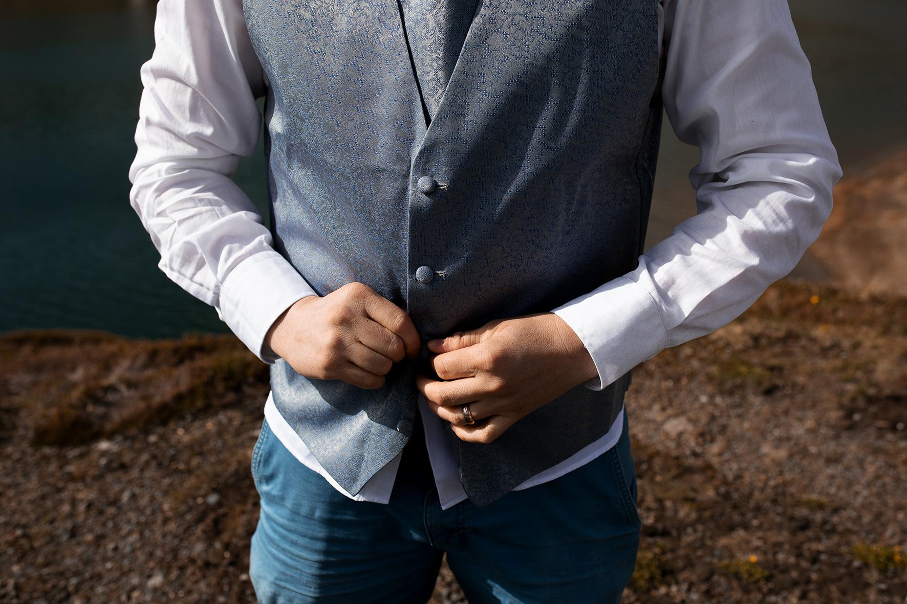 Der Bräutigam bereitet sich für die Trauung zu Zweit in den Schweizer Bergen vor. Er trägt ein weisses Hemd und knüpft sich seine blaue Veste zu. Im Hintergrund zu erahnen der Bergsee.